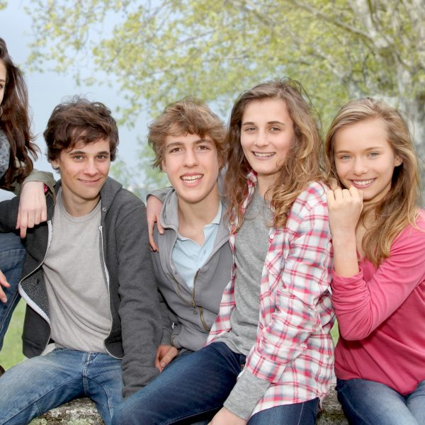 Group of teenagers sitting outside